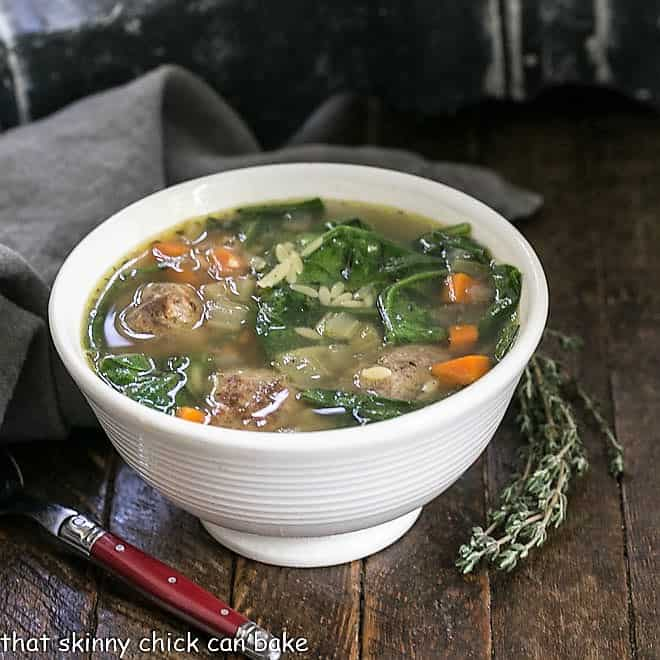 Italian wedding soup in a white bowl with a sprig of thyme