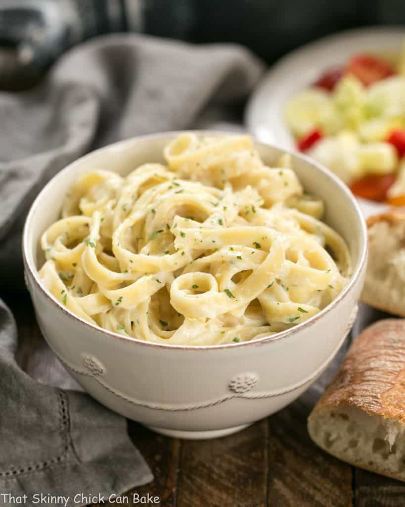 Light Fettuccine Alfredo in a white bowl with bread and salad in the back ground