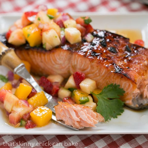 Maple Glazed Salmon on a white plate with a forkful of salmon next to a larger piece of salmon
