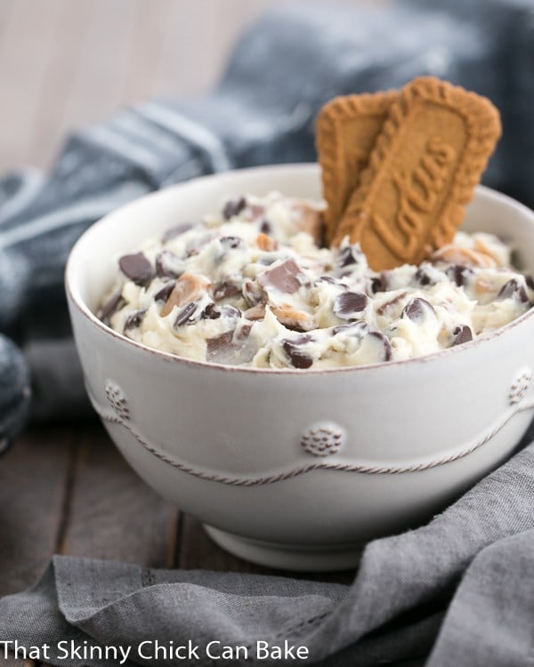 Chocolate Chip Cookie Dough Dip in  a white bowl garnished with 2 Biscoff cookies