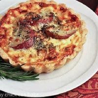 Blue Cheese and Potato Tartlet ona white plate with a sprig of rosemary