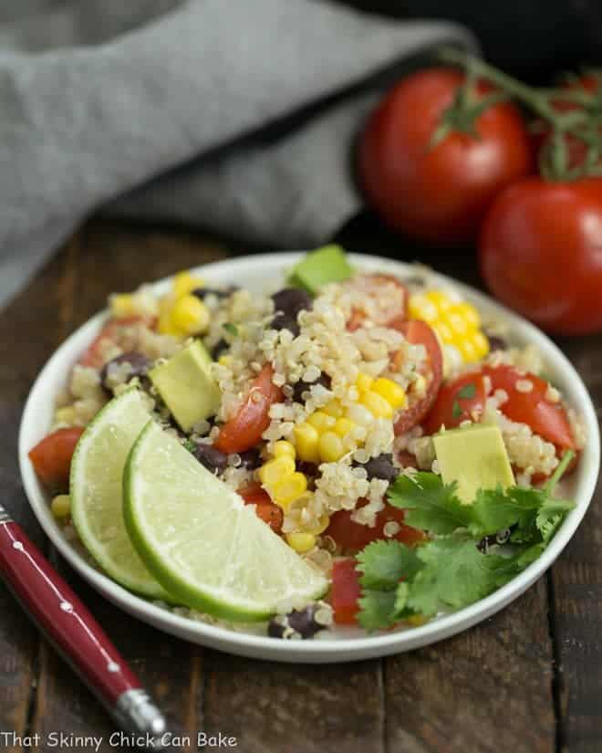 Quinoa Black Bean Salad with Lime Cumin Vinaigrette on a small white plate with a lime garnish