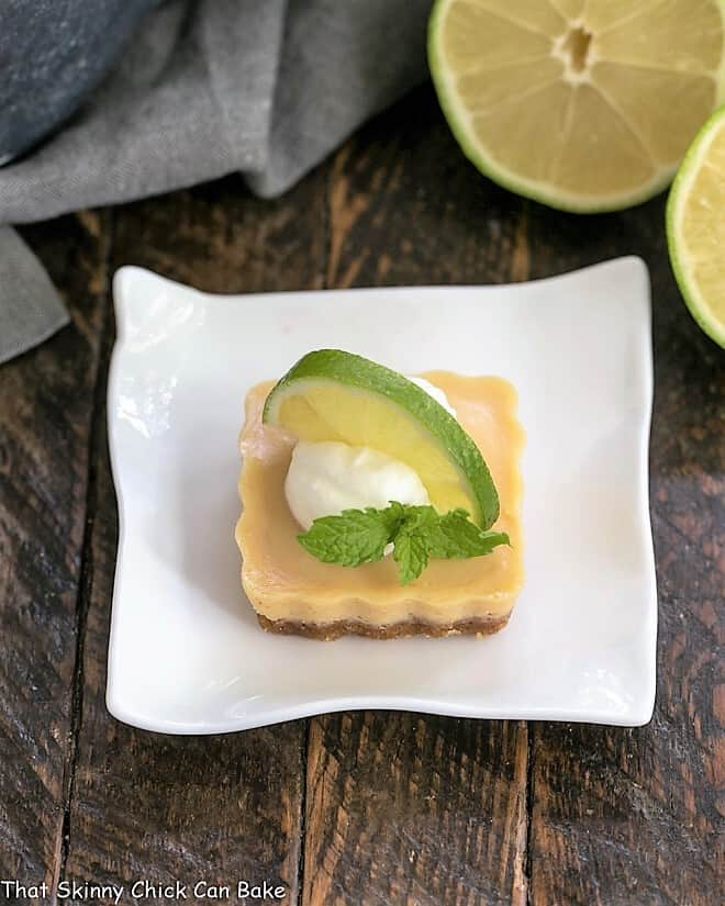 Key Lime Tartlet on a white plate with whipped cream and a slice of lime