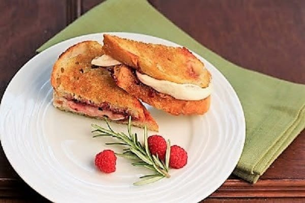 Mozzarella Grilled Cheese with Raspberries and Brown Sugar on a white plate with raspberries and rosemary garnish