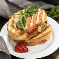 Strawberry, Turkey and Brie Grilled Cheese on a white lunch plate