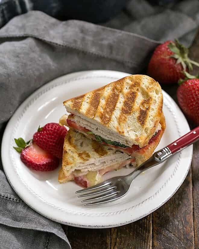 Strawberry, Turkey and Brie Grilled Cheese stacked on a white lunch plate with a red handled fork
