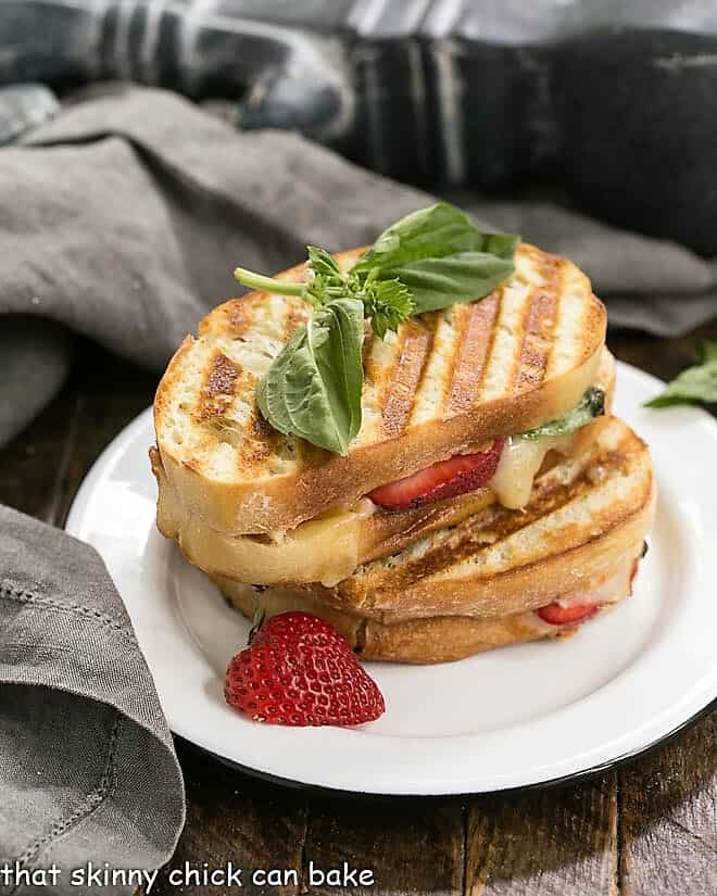 Strawberry, Turkey and Brie Grilled Cheese halves stacked on a round white plate with basil and strawberry garnish