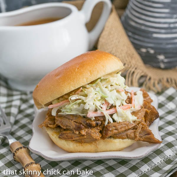 Pulled Pork Sandwiches on buns topped with coleslaw with a pitcher of BBQ sauce