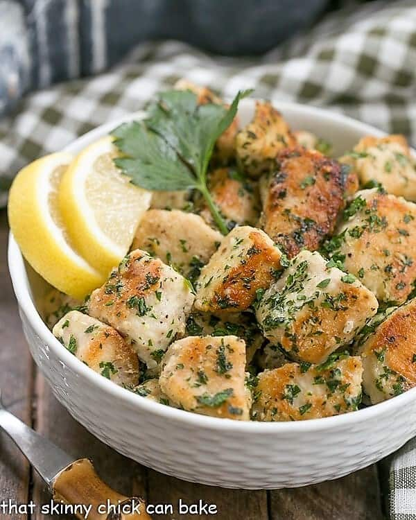 Chicken with Garlic and Parsley in a white basket weave bowl garnished with lemons and a sprig of parsley