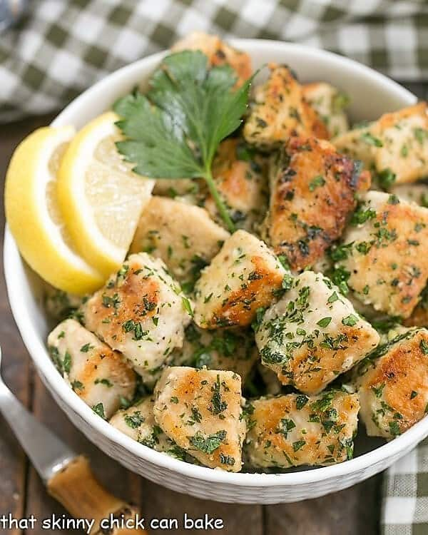 Chicken with Garlic and Parsley with lemon slices in a white bowl