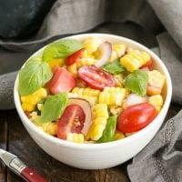 Small white bowl filled with fresh corn, basil and tomato salad