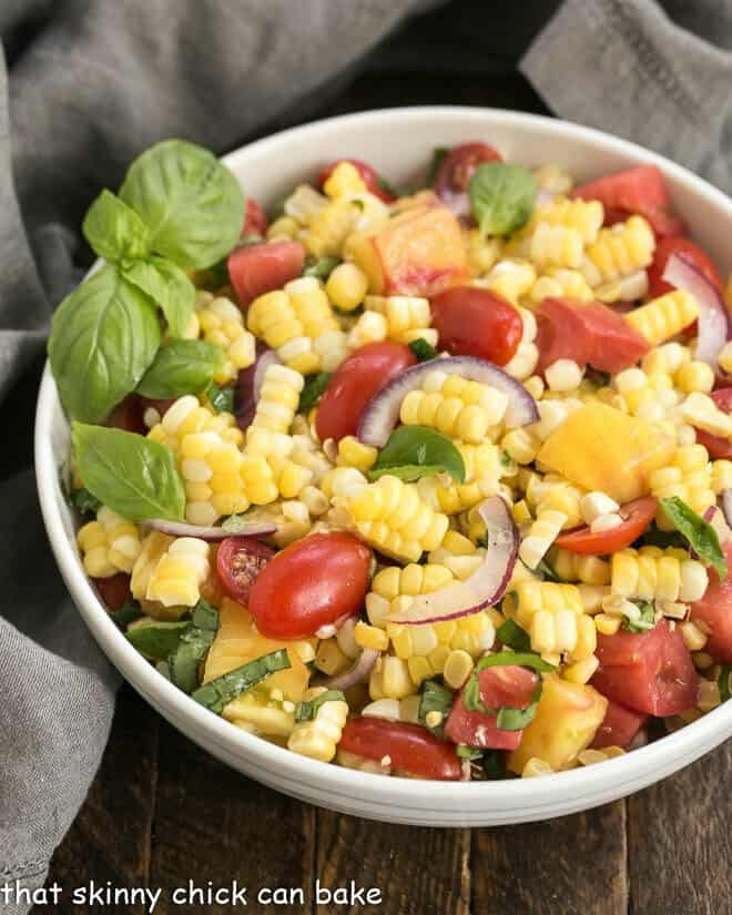 Overhead view of fresh corn and tomato salad in a white serving bowl