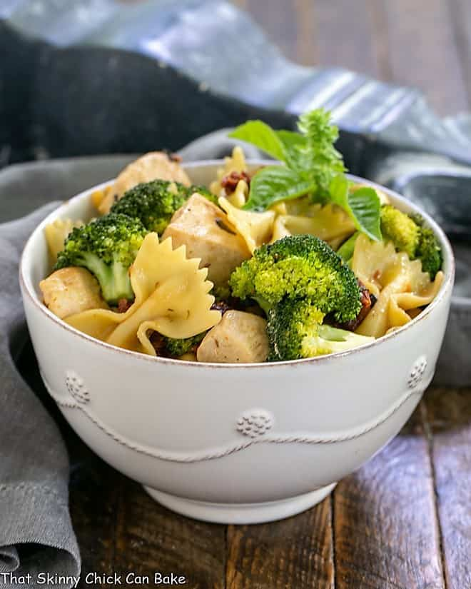 Chicken with Broccoli, Sun-dried Tomatoes and Bow Tie Pasta in a white ceramic bowl