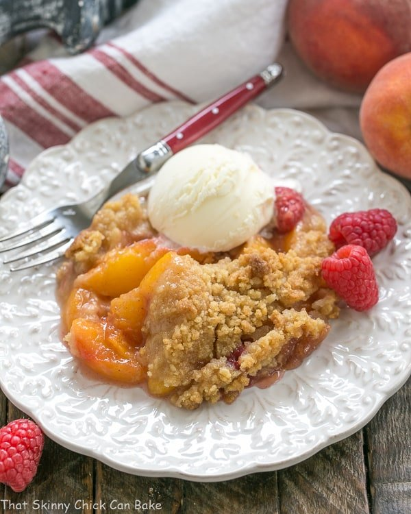 Peach Raspberry Crisp on a white plate topped with a scoop of ice cream