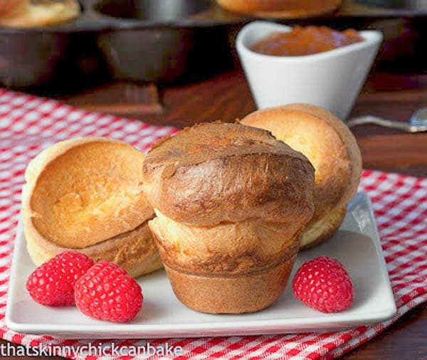 Perfect Popovers on a square white plate with fresh raspberries