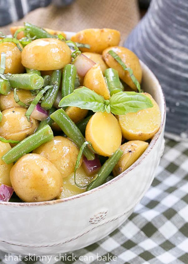 Close view of a Potato and Green Bean Salad with Dijon Vinaigrette in a bowl with a basil garnish