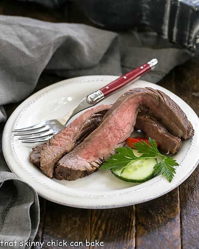 Slices of flank steak on a white plate with a red handled fork