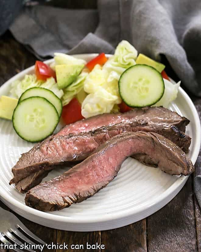 Easy Marinated Flank Steak slices on a white plate