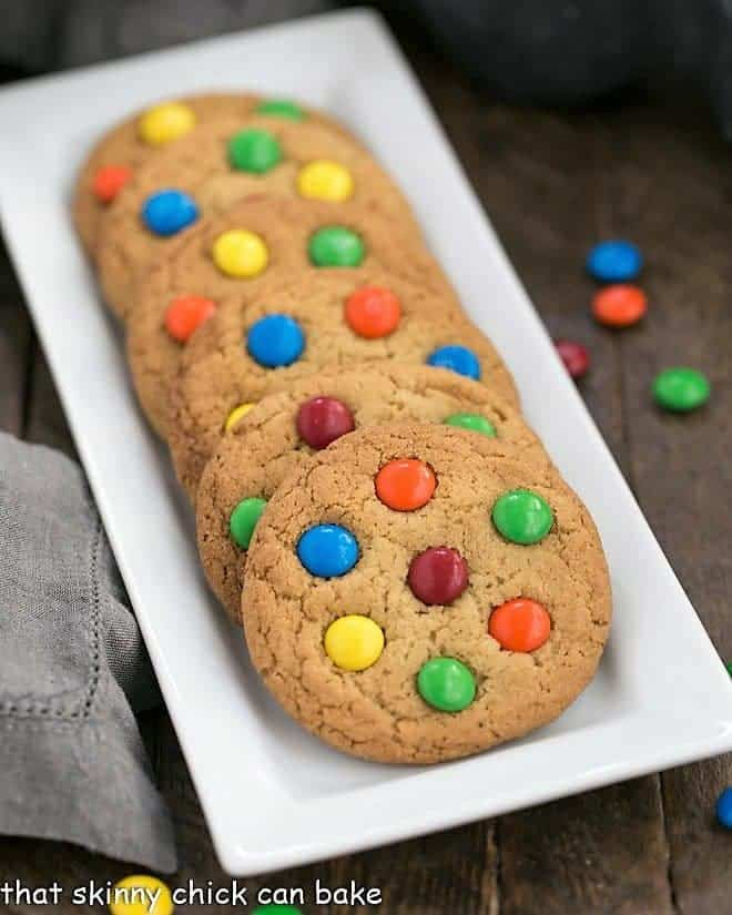 Classic M & M Cookies lined up on a white rectangualr tray