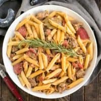 Creamy Italian Sausage Pasta with a sprig of rosemary in a white serving bowl
