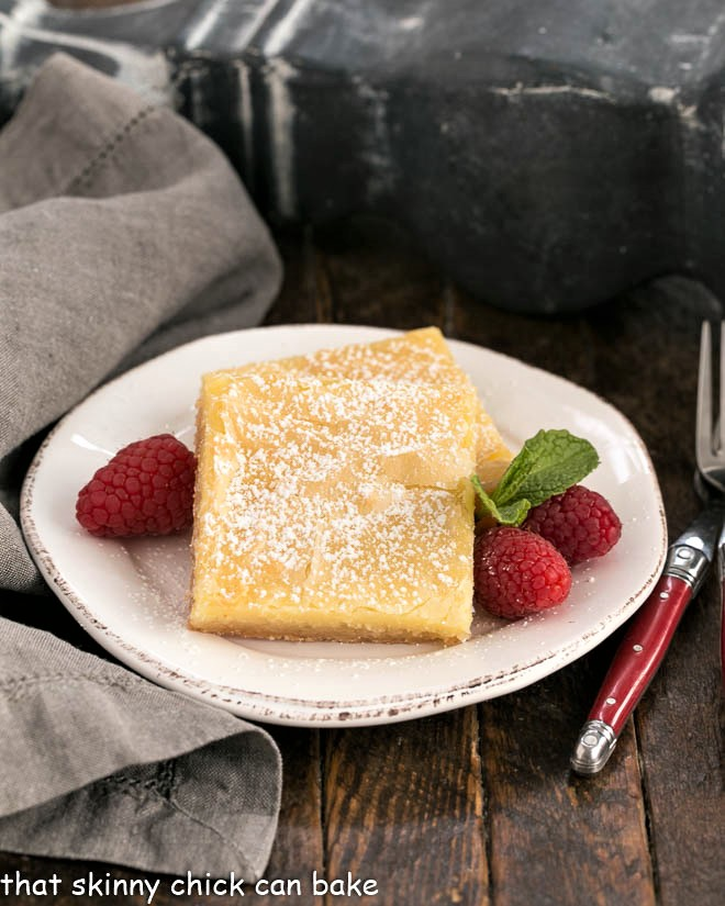 Two gooey butter bars on a round white plate with fresh raspberries and mint