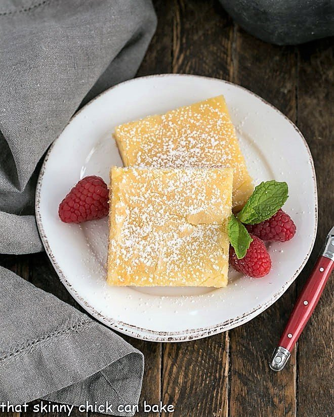 Overhead view of gooey butter cake slices on a white plate with raspberries