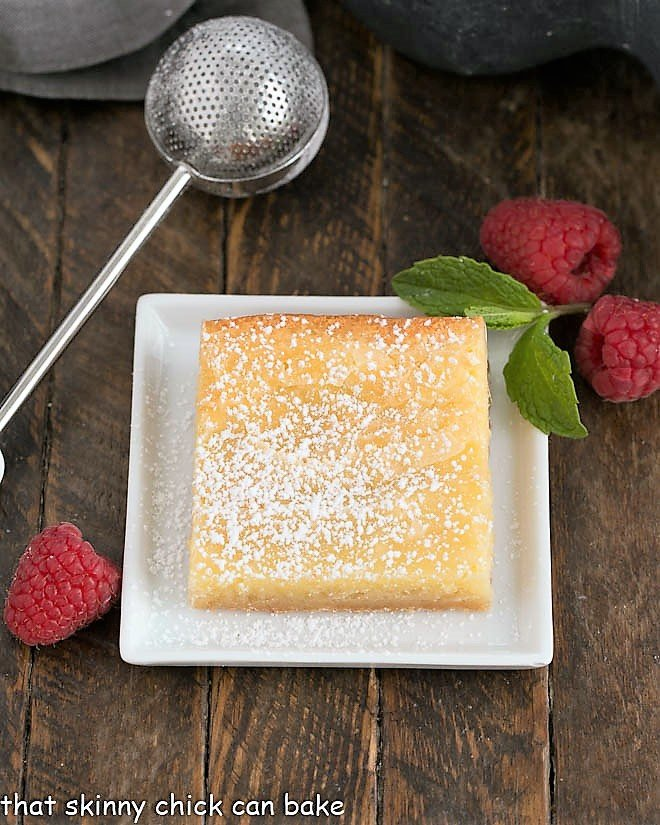 One slice of gooey bars on a square white plate with a powdered sugar duster