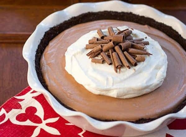 Candy Bar Pie garnished with chocollate in a large white pie dish.