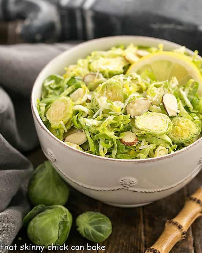 Shaved Brussels Sprouts Salad in a white salad bowl with a lemon slice and a bamboo handled fork