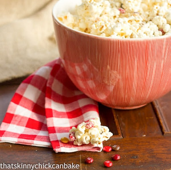 Holiday White Chocolate Popcorn in a red and white striped ceramic bowl