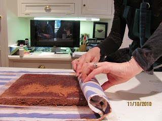 rolling chocolate cake into a towel to make a cake roll