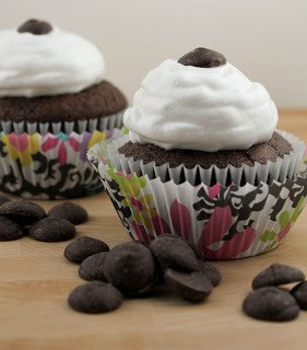 Cocoa Cupcakes with Ganache Filling on a wood board with chocolate chips
