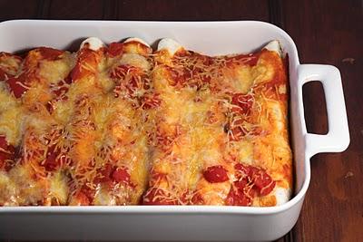 Chicken enchiladas in a white casserole dish