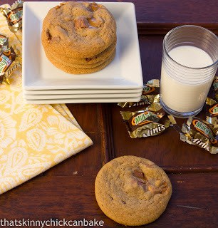 Milky Way Cookies on a stack of white serving plates next to Milky Way wrappers and a glass of milk.
