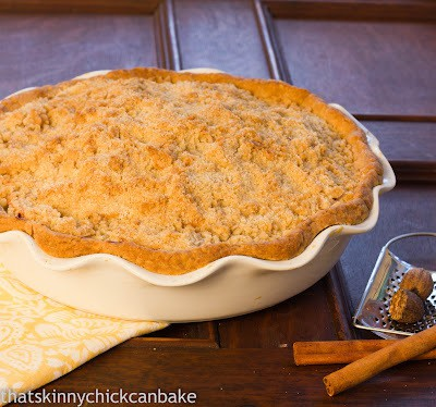Crumb Topped Apple Pie in large pie dish with cinnamon sticks on the side.