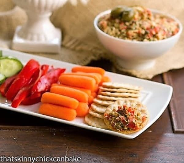 Crudite and crackers in front of a bowl of red pepper artichoke tapenade
