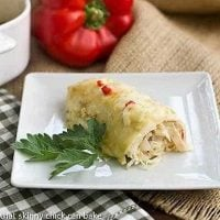 Creamy Chicken Enchiladas on a square white plate with a sprig of parsley