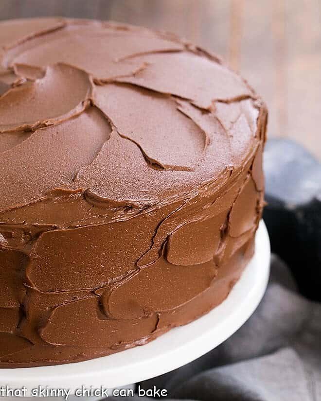 Chocolate Layer Cake with Ganache on a white ceramic cake stand