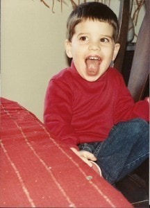The birthday boy as a child in a red shirt and jeans with a big smile