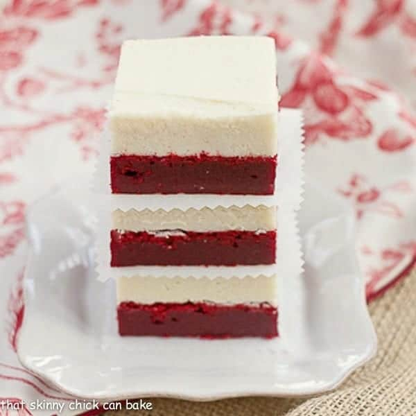 Red Velvet Brownies with White Chocolate Icing stacked on a square white plate