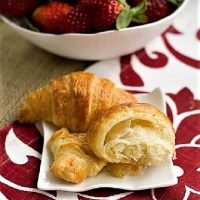 Homemade Classic Croissants on a small white ceramic plate with a bowl of strawberries