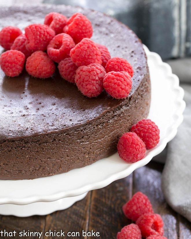 Chocolate Kahlua Cake on a white cake stand topped with fresh raspberries