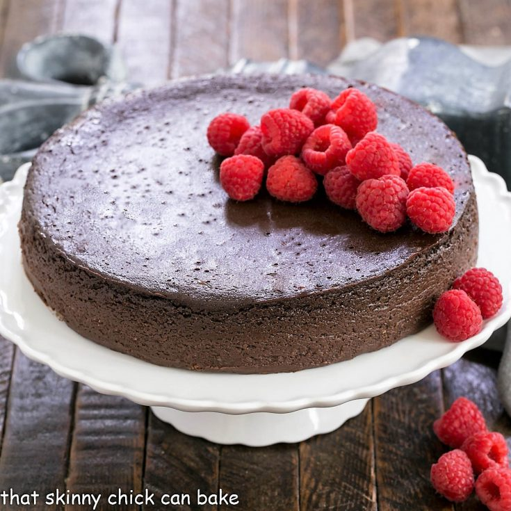 Flourless Kahlua cake on a white cake stand topped with raspberries
