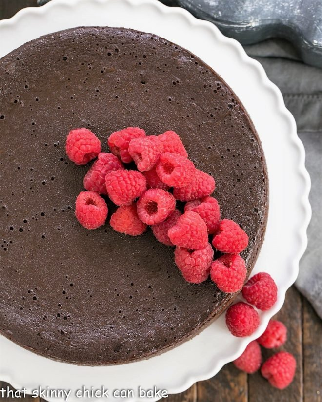 Overhead view of Flourless Chocolate Kahlua Cake topped with raspberries on a cake stand