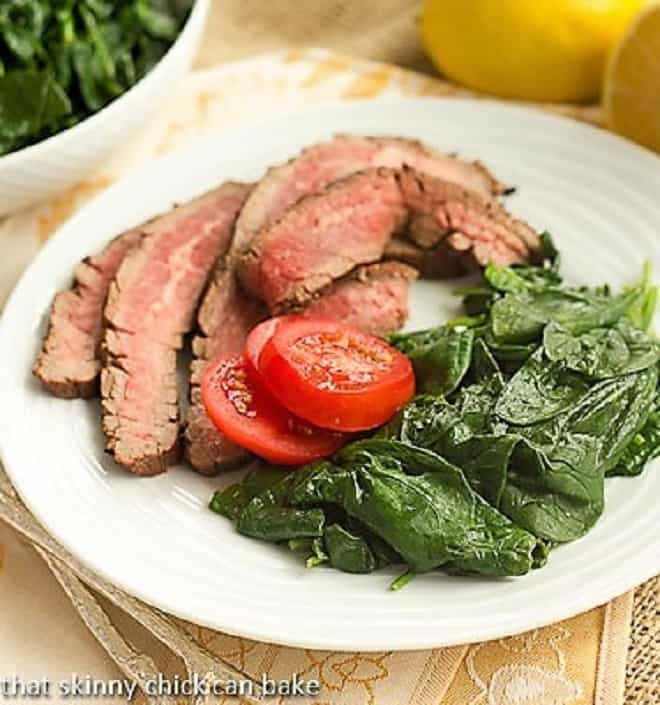 Lemon Steamed Spinach on a white dinner plate garnished with fresh tomatoes
