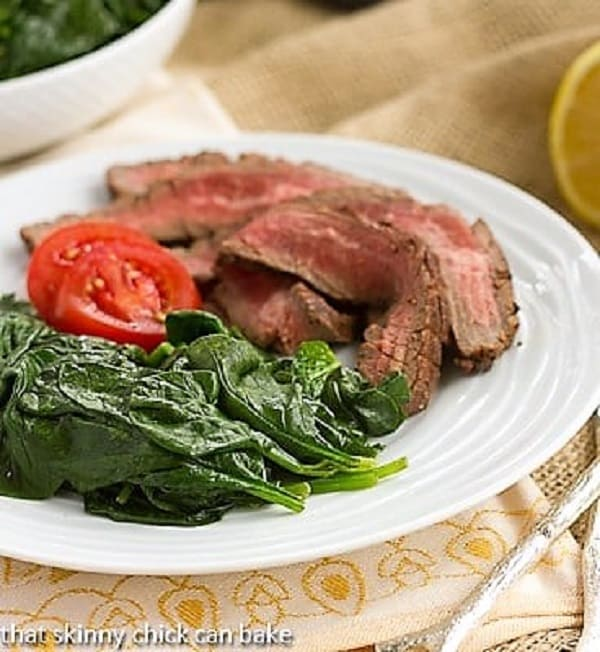 Easy Lemon Spinach  with flank steak on a white plate