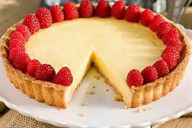 Tarte au Citron AKA French Lemon Tart on a cake stand with a slice removed