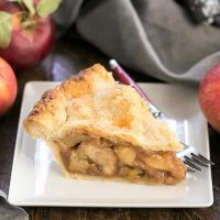 Slice of caramel apple pie on a square white plate