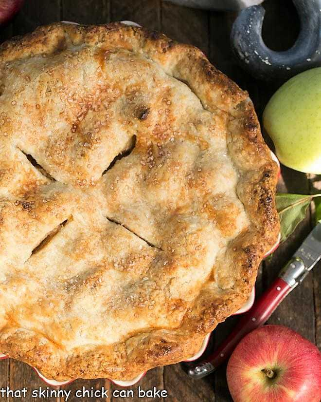 Overhead view of whole Caramel Apple Pie with apples and a red handle knife