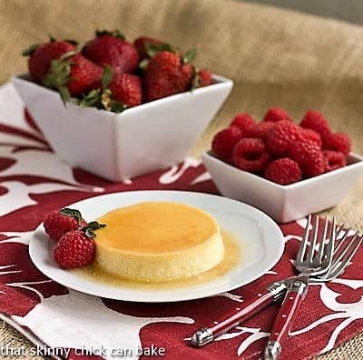 Classic Flan on a  white plate in front of bowls of raspberries and strawberries